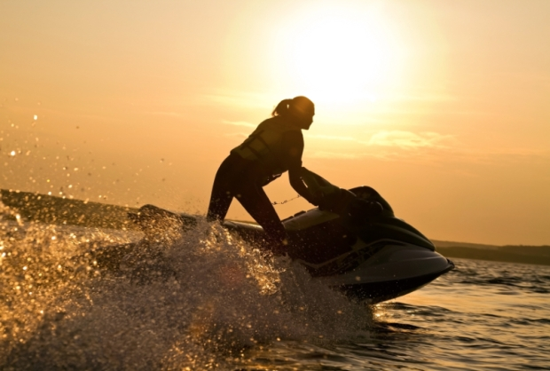 beautiful girl riding her jet skis in the sea at sunset . spray